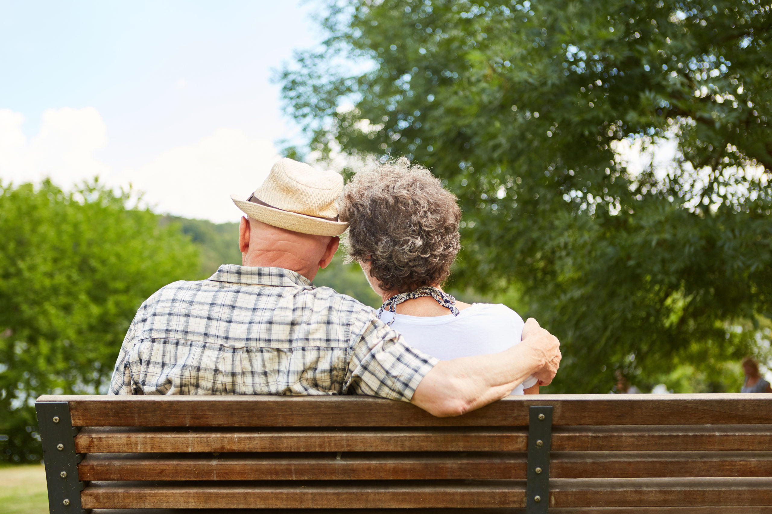Senior couple sitting side by side on a park bench as a sign of harmony and love